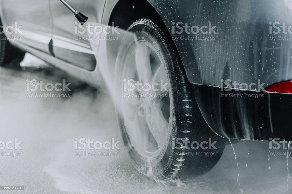 Limpiar el coche con agua a alta presión. Enfoque suave. Poca profundidad DOF - foto de stock