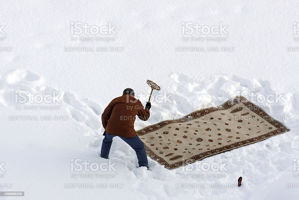 Cleaning carpet in snow stock photo