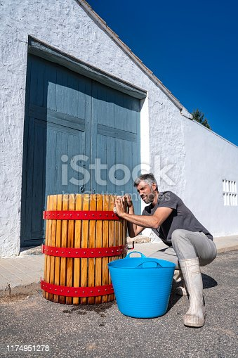 Winemaker man cleaning cellar wooden wine press outdoor with water in Mediterranean