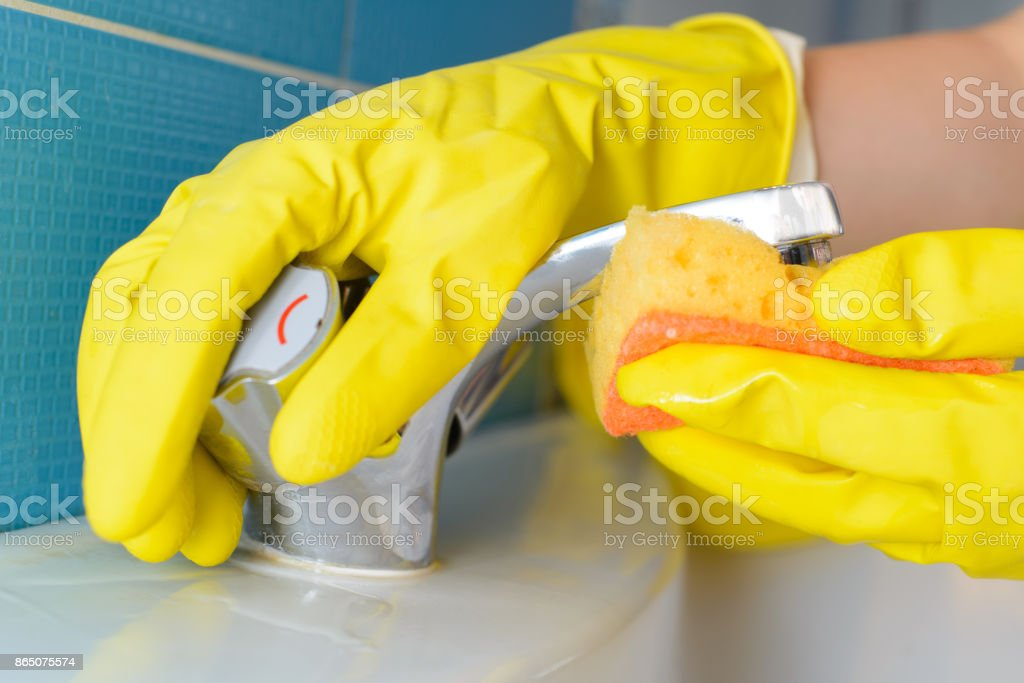 Cleaning - cleaning bathroom sink and faucet with detergent in yellow...