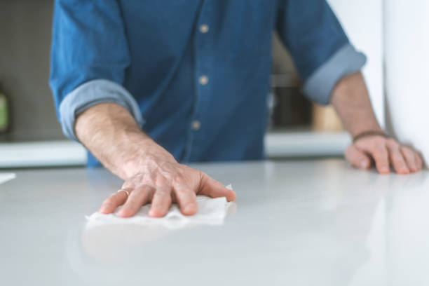 Cleaning counter with disinfecting wipe Close-up shot of man using a disinfecting wipe to clean a kitchen counter. The modern kitchen has a white counter. The man is wearing a casual shirt with sleeves rolled up. rubbing stock pictures, royalty-free photos & images