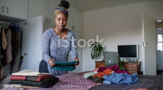 Cropped shot of a young woman folding her laundry at home