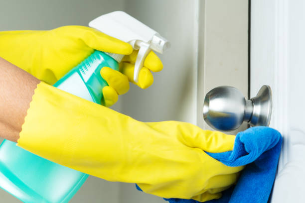 Cleaning door knob with alcohol spray for Covid-19 Coronavirus prevention stock photo