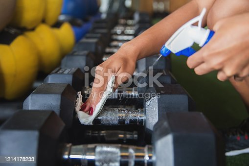 Close up shot female hands cleaning dumbbells before workout ,precautions of Coronavirus