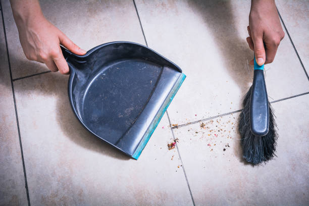 cleaning dust on tile floor with brush and dustpan holded by female hands, high angle view - sweeping stock pictures, royalty-free photos & images