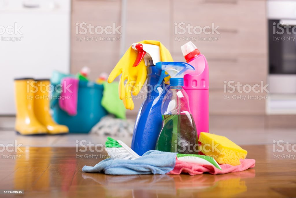 Close up of cleaning products and tools on kitchen floor with bucket,...