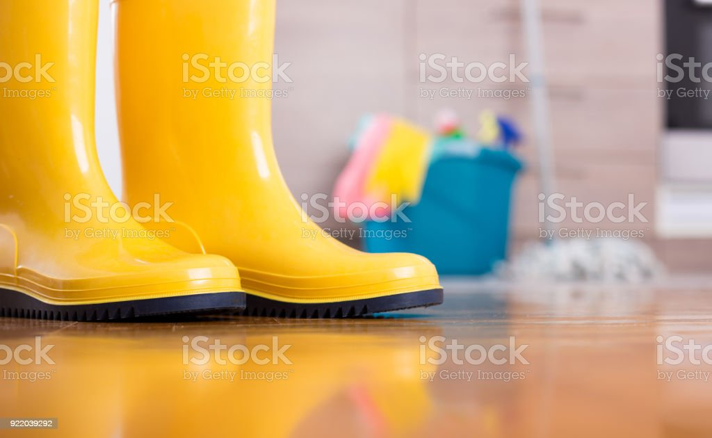 Close up of yellow gumboots on floor with bucket, mop and cleaning...