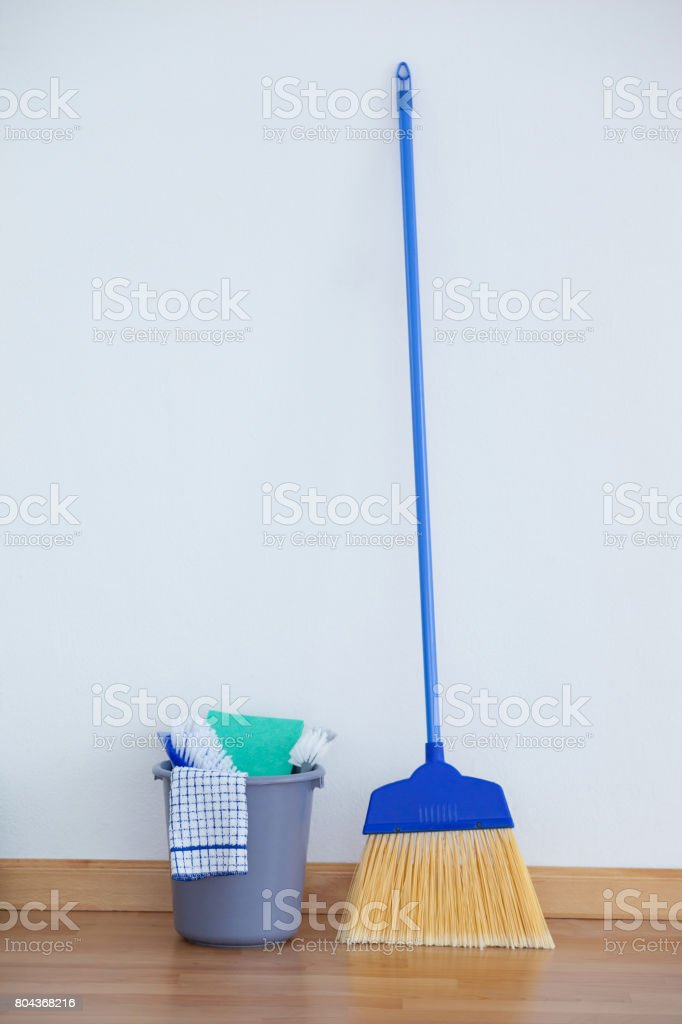 Various cleaning equipment on wooden floor against wall