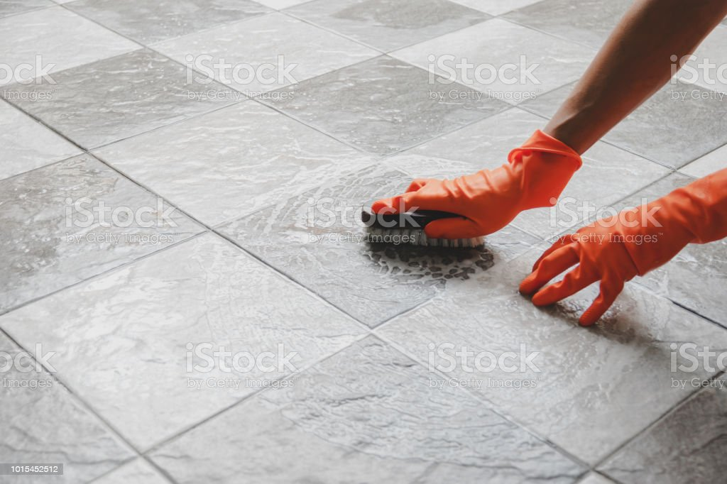 Cleaning Equipment & Supplies Hand of man wearing orange rubber gloves is used to convert scrub cleaning on the tile floor. Adult Stock Photo