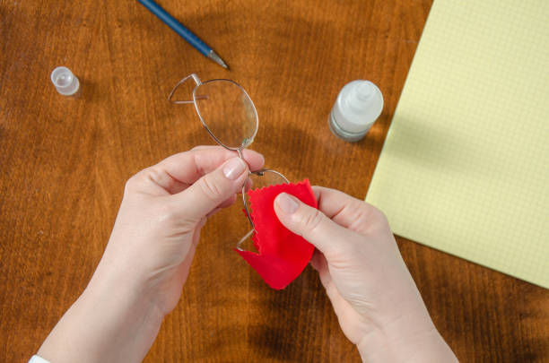Cleaning eyeglasses with a red soft cloth stock photo