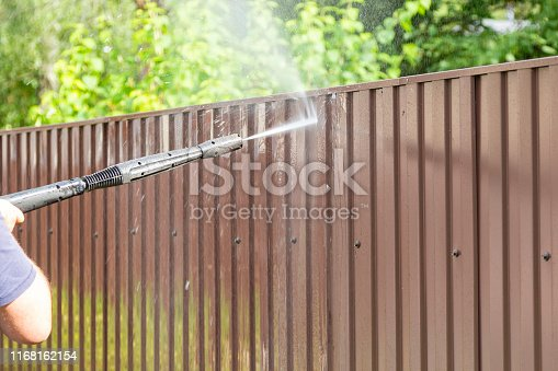 Cleaning fence with high pressure power washer, cleaning dirty wall.