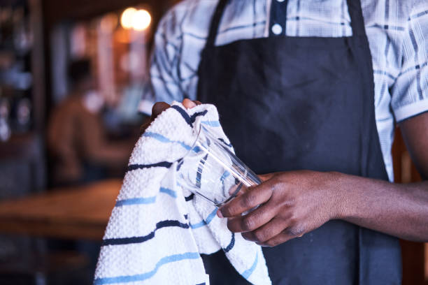 Cleaning glass wear African black waiter cleaning a glass with a dish cloth wearing a blue button up shirt and black apron Randburg, Johannesburg, Gauteng South Africa old man working in a pub stock pictures, royalty-free photos & images