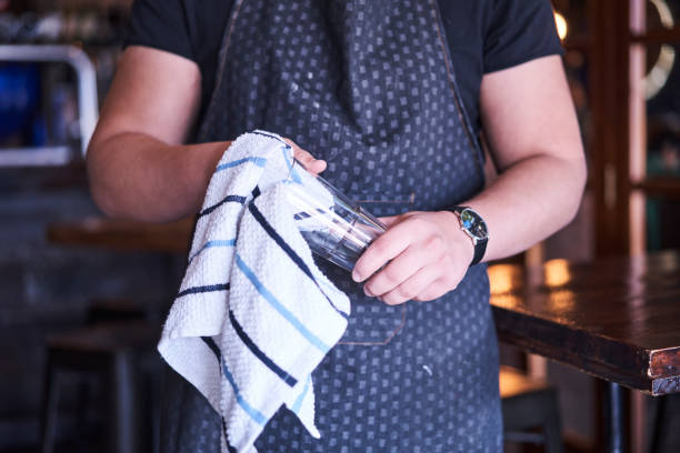 Cleaning glassware Caucasian waiter cleaning a glass with dish cloth wearing a wrist watch, black shirt and blue apron Randburg, Johannesburg, Gauteng South Africa old man working in a pub stock pictures, royalty-free photos & images