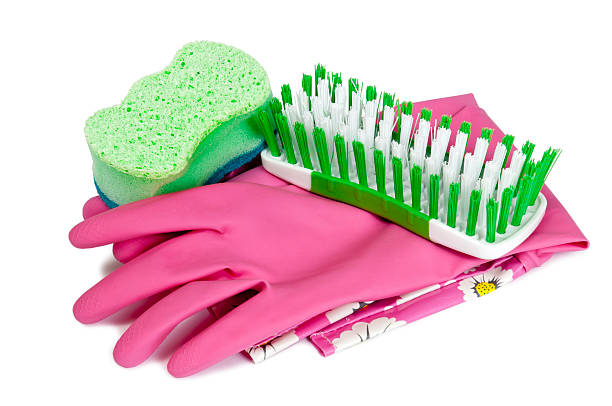 Cleaning Gloves With Sponge And Brush Colorful cleaning gloves with a green sponge and brush ready to use.  Isolated on white with shadows under gloves.  Shot in studio on white background.  Horizontal shot. scrubbing brush stock pictures, royalty-free photos & images