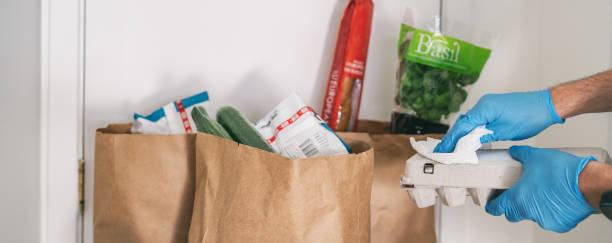 Cleaning groceries with disinfecting wipes as coronavirus prevention. Man wiping down grocery packages after receiving home delivery wearing gloves to wipe the surfaces clean. Cleaning of COVID-19 stock photo