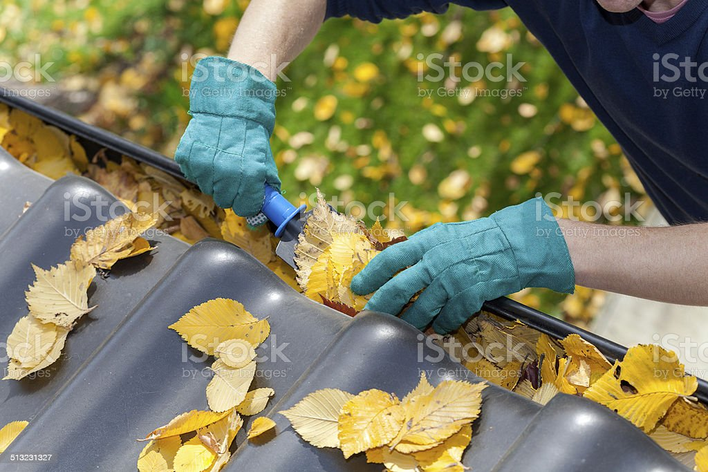 Cleaning gutters from leaves stock photo