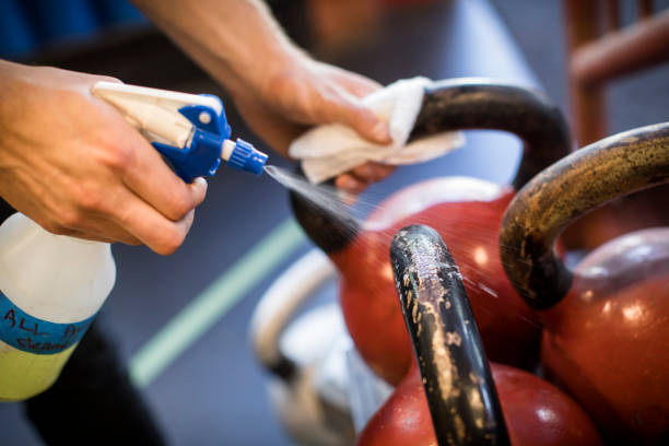 Cleaning gym equipment after workout.