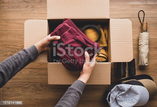 Cleaning home and donation concepts with young person putting accessories clothing in brown box.giving and sharing with human.second hand or recycle product ideas