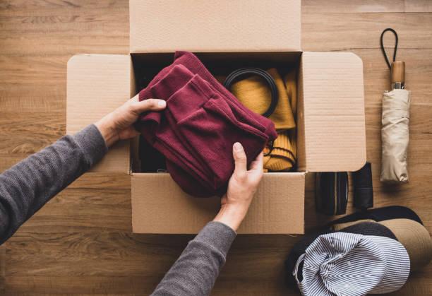 sprzątanie domu i darowizny koncepcji z młodym człowiekiem wprowadzenie akcesoriów odzież w brązowy box.giving i dzielenie się z ludźmi - odzież zdjęcia i obrazy z banku zdjęć