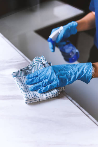 Cleaning home table sanitizing kitchen table surface with disinfectant spray stock photo