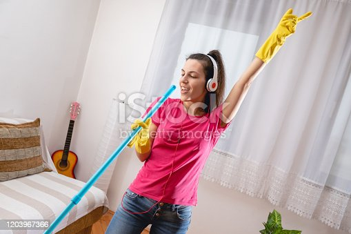 1081403344 istock photo Cleaning house and listening to the music 1203967366