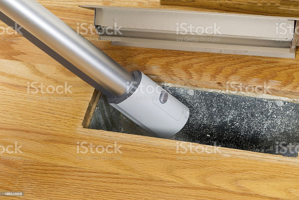 Cleaning inside heating floor vent with Vacuum Cleaner Horizontal photo of vacuum cleaning inside heater floor vent with Red Oak Floors in background Air Duct Stock Photo