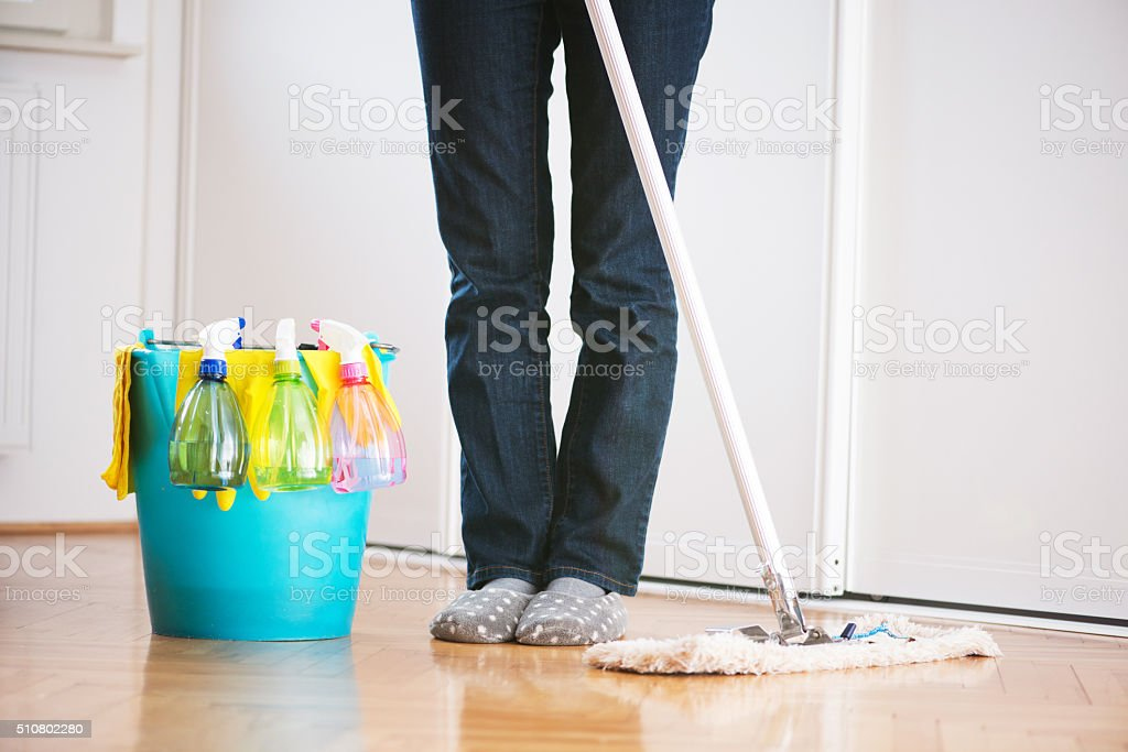 Cleaning kitchen floor with mop, bucket and cleaning products, legs...