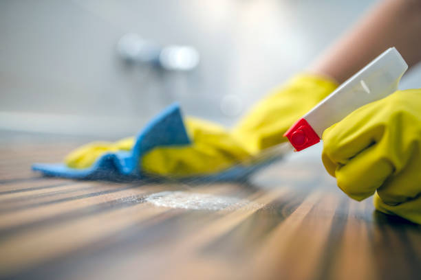 Cleaning kitchen table  with blue cloth Photo of Woman or man cleaning kitchen cabinets with sponge and spray cleaner. Female or male hands Using Spray Cleaner On Wooden Surface. Maid wiping dust while cleaning her house wearing yellow protective gloves, close-up cleaning equipment stock pictures, royalty-free photos & images