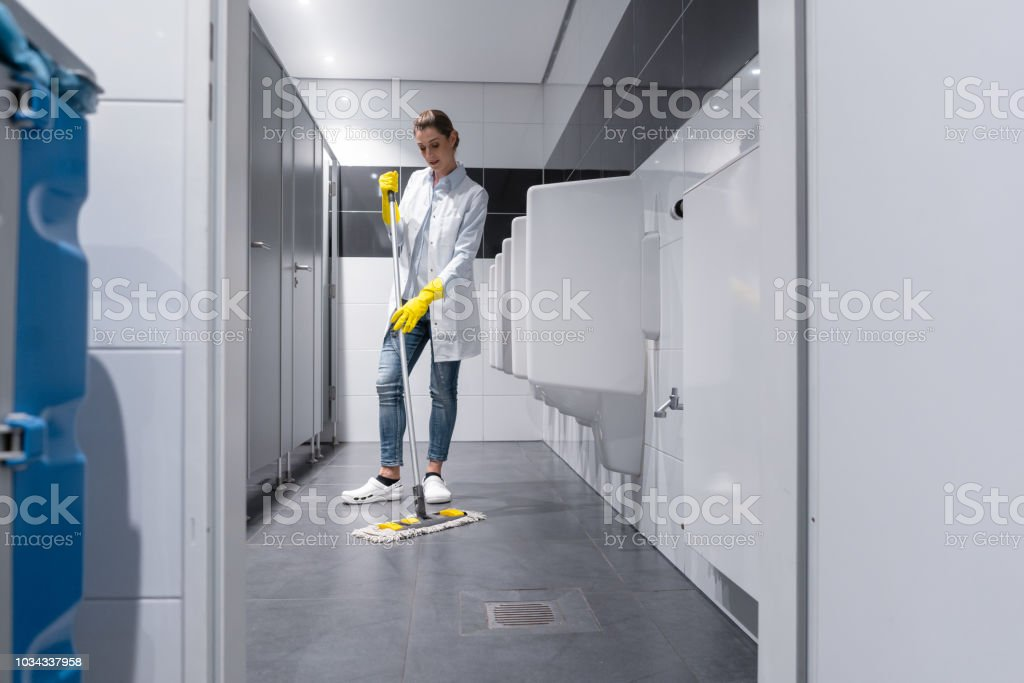 Cleaning lady mopping the floor in men's restroom stock photo