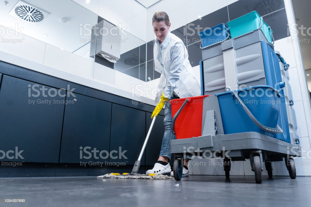 Cleaning lady mopping the floor in restroom stock photo