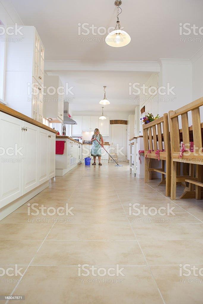 A middle-aged cleaner mopping the tiles floor of a large domestic...