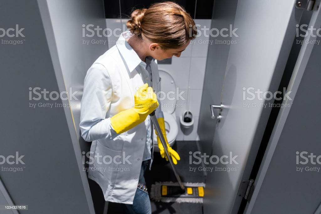 Cleaning lady or janitor mopping the floor in restroom stock photo