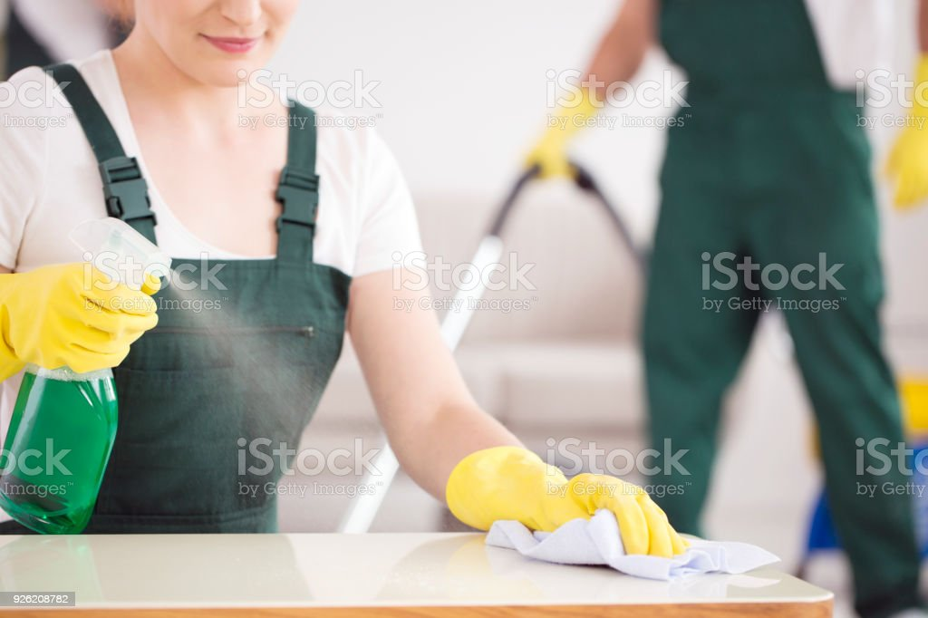 Cleaning lady spraying table stock photo
