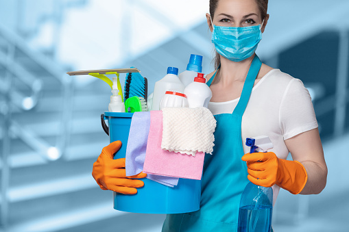 Cleaning lady with tool in cleaning in mask on a blurred background.