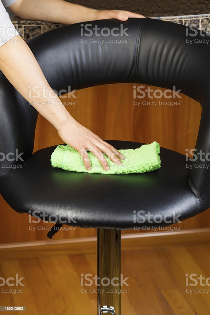 Cleaning Leather Kitchen Chair with microfiber rag royalty-free stock photo