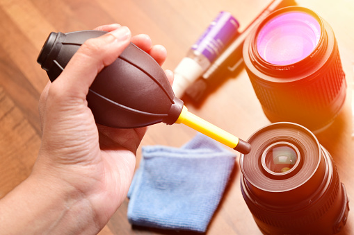 cleaning lens from air blower, hand holding camera air blower for cleaning lens