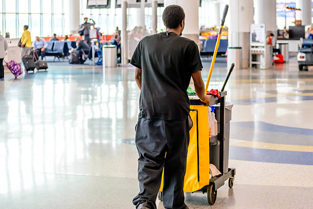 cleaning man pushing cart in an airport stock photo