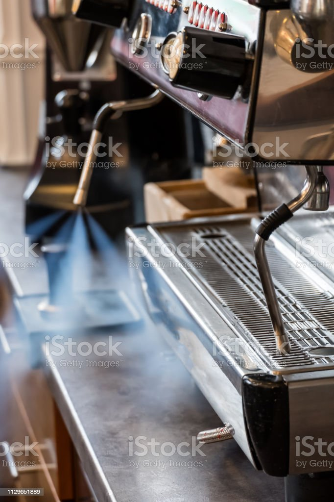 Cleaning milk frother of coffee machine with water steam jet to be...