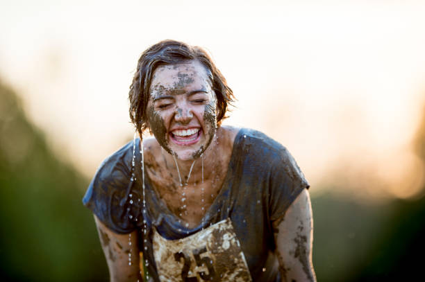 Cleaning Off With Water A Caucasian woman is standing outdoors. She has just completed a mud run. She is puring water on her face to clean off. mud run stock pictures, royalty-free photos & images