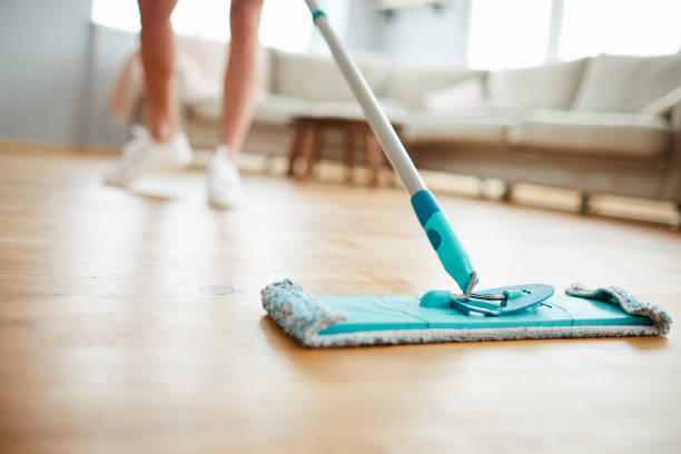 Cleaning parquet floor Close-up of unrecognizable woman using mop with microfiber pad while cleaning parquet floor in living room mop stock pictures, royalty-free photos & images