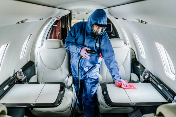 A cleaning person in blue protective suit wiping down surfaces aboard an airplane before flight stock photo