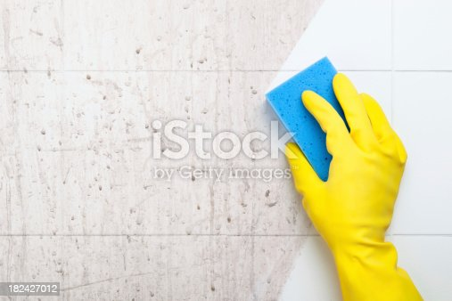 Closeup of a hand in a yellow rubber glove cleaning a dirty bathroom surface with a blue sponge.