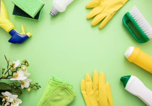 Cleaning products background, detergent bottles and tools Household cleaning eco spring background. Cleaning products flat lay, chemical detergent bottles and fresh blossoms on green color background, cleaning equipment stock pictures, royalty-free photos & images