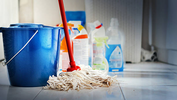 Cleaning products. Closeup of unrdcognizable home cleaning products with blue bucket and a mop in front in sharp focus. All products placed on white and poorly lit bathroom floor. cleaning equipment stock pictures, royalty-free photos & images