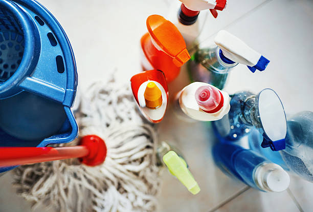 Cleaning products. Closeup top view of unrecognizable home cleaning products with blue bucket and a mop on the side. All products placed on white tiled bathroom floor. cleaning equipment stock pictures, royalty-free photos & images