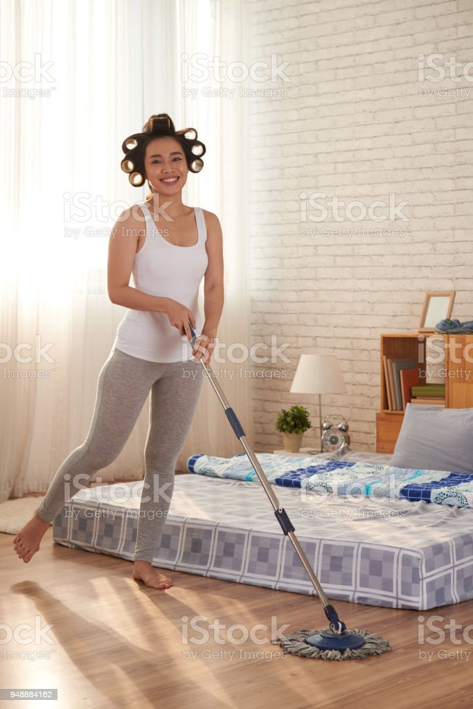 Beautiful young Vietnamese woman cleaning floor in her room