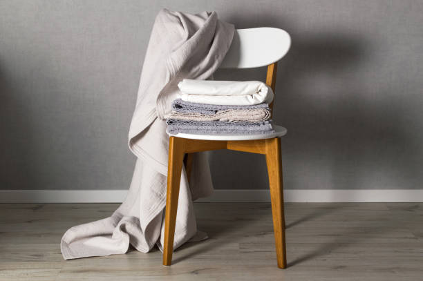 Cleaning service. Stack of grey linen on the chair