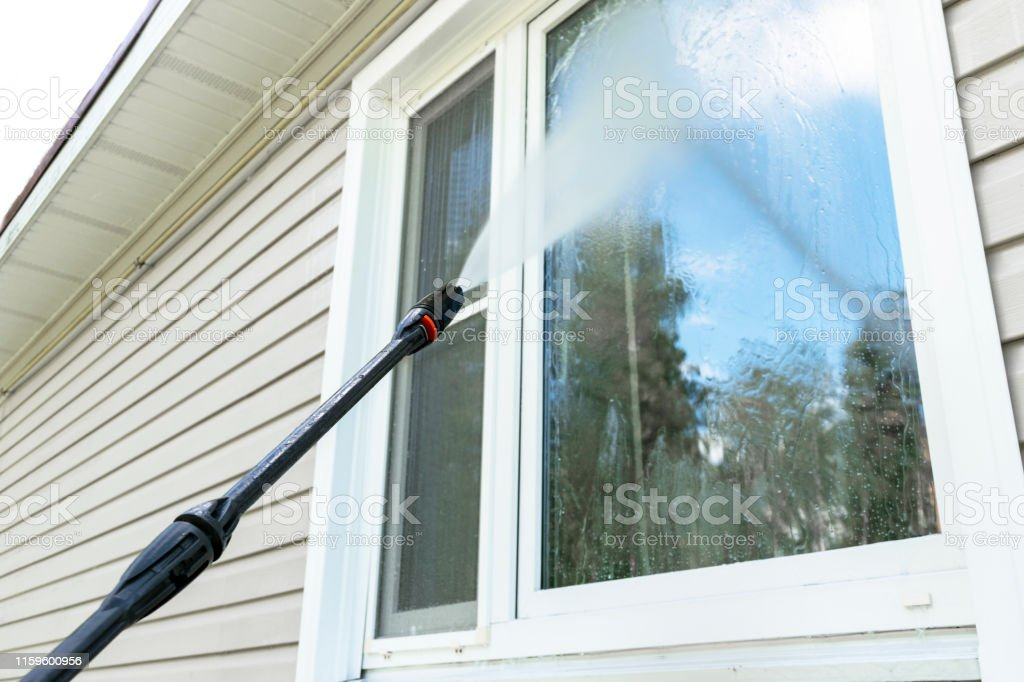 Cleaning service washing building facade and window with pressure...