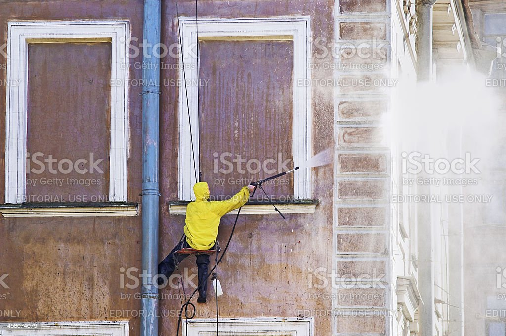 Cleaning service worker washing old building facade stock photo