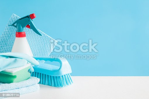 istock Cleaning set for different surfaces in kitchen, bathroom and other rooms. Empty place for text or logo on blue background. Cleaning service concept. Early spring regular clean up. Front view. 918825114
